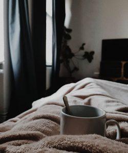 white-ceramic-mug-on-bed